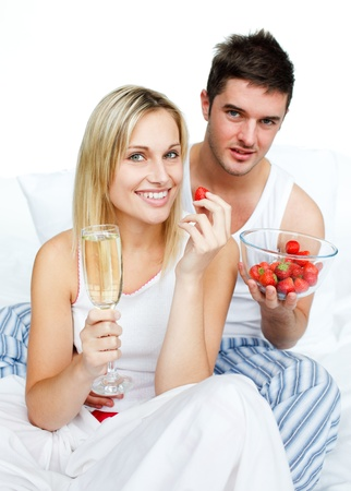 Couple celebrating an engagement with strawberries and champagne photo