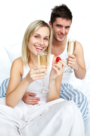 Happy man and woman celebrating an engagement with champagne photo