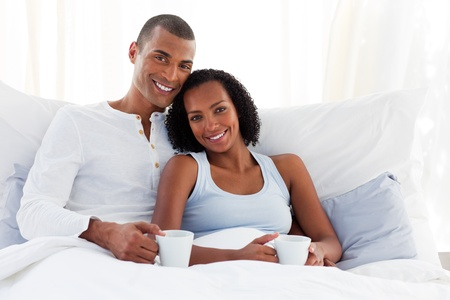 Afro-american couple drinking a coffee on their bed photo