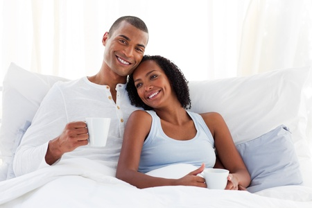 Romantic couple drinking a coffee on their bed photo