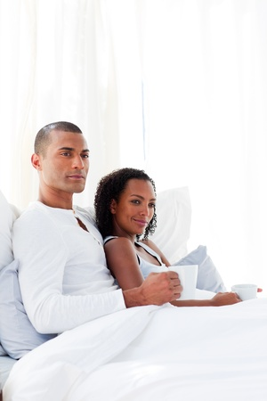Loving couple drinking a coffee on their bed photo