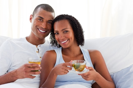 Smiling couple drinking a cup of tea on their bed Stock Photo - 10258393