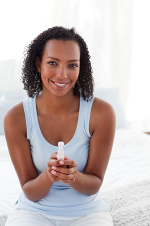 finding out: Smiling woman finding out results of a pregnancy test