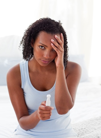 finding out: Diconcerted woman finding out results of a pregnancy test