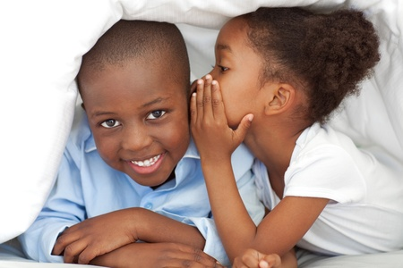 Cute little girl whispering something to her brother photo