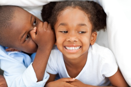 Ethnic little boy whispering something to his sister  photo