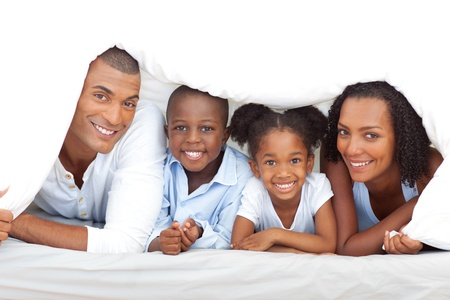 Merry family having fun lying down on bed photo
