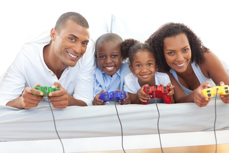 Animated family playing video game lying down on bed Stock Photo - 10259076
