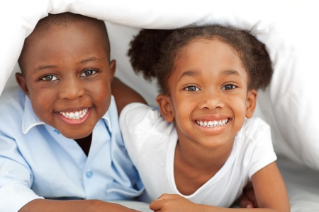 convivial: Portrait of ethnic siblings lying down on bed Stock Photo