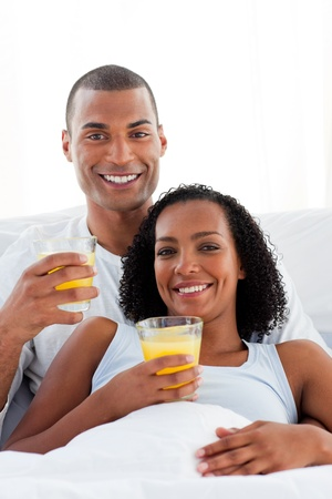 Enamored couple drinking lying on their bed photo