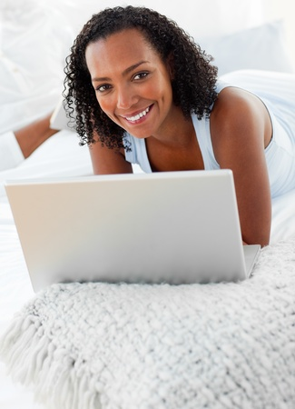 Cheerful woman using a laptop on her bed photo