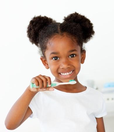 cepillarse los dientes: Retrato de una chica afroamericana cepillarse sus dientes