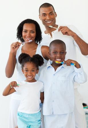 Smiling family brushing their teeth photo