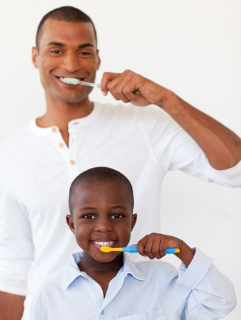 Father and his son brushing their teeth photo