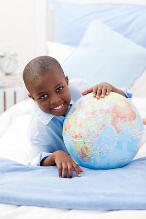 Boy looking at a globe while smiling at the camera photo