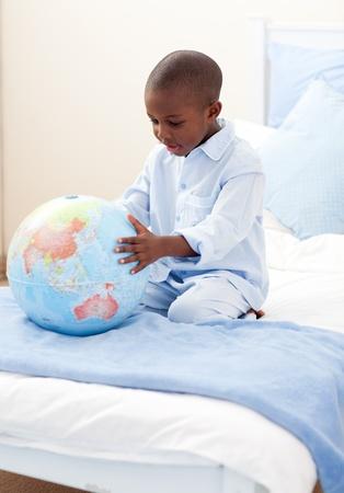 terrestrial globe: Little boy holding a terrestrial globe