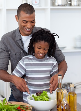 Adorable little boy preparing salad with his father photo