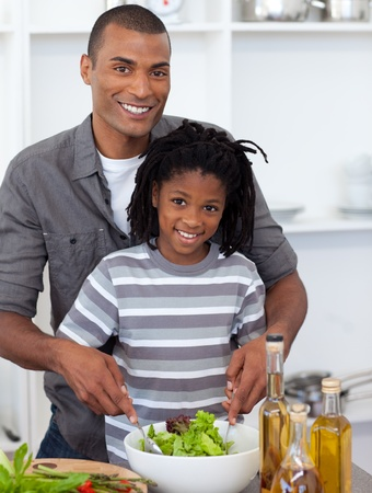Smiling little boy preparing salad with his father photo