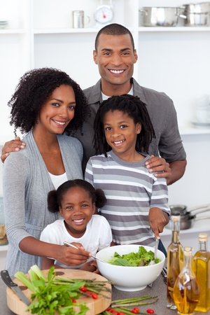 Ethnic family preparing salad together photo