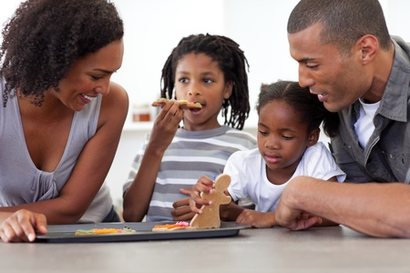 Happy afro-american family eating homemade biscuits  photo