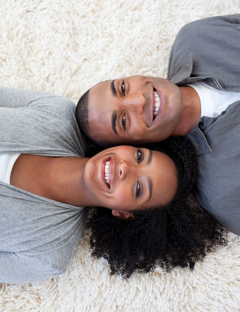 Smiling Afro-American couple lying on the floor Stock Photo - 10222051