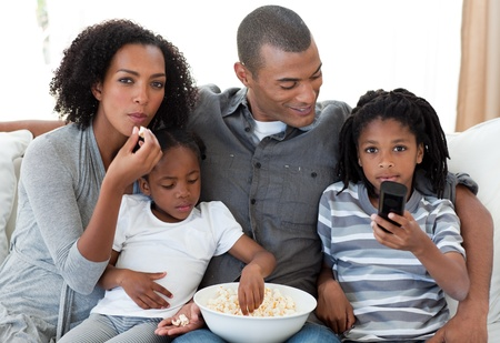 Afro-American family watching a film at home photo