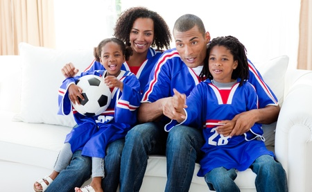 Afro-American family watching a football match at home Stock Photo - 10258519