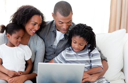 Afro-American family using a laptop on the sofa photo