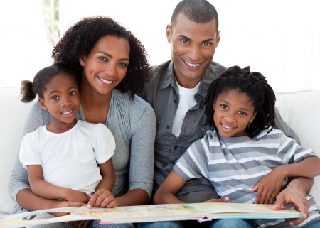 Portrait of an Afro-American family reading a book in the living-room Stock Photo - 10238802