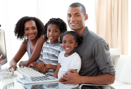 ethnic children: Happy Afro-American family working with a computer at home