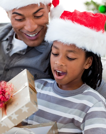 Portrait of an Afro-American father and son opening a Christmas gift photo