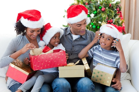 Happy Afro-American family playing with Christmas presents photo