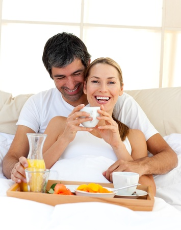 Loving couple having breakfast lying in the bed photo