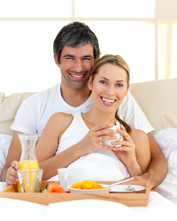 Smiling couple having breakfast lying in the bed photo