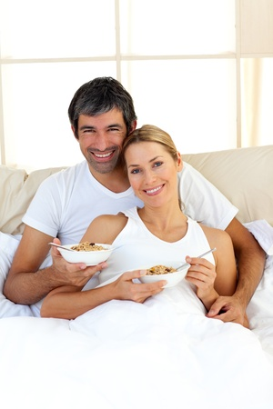Blond woman and her boyfriend eating cerelals photo