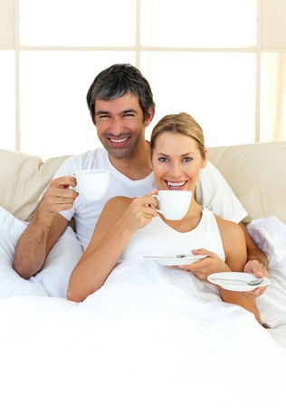 Enthusiastic lovers drinking coffee lying in the bed photo