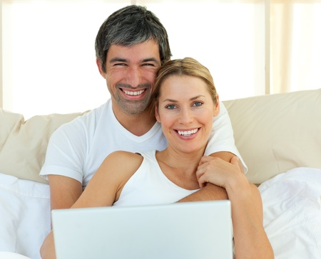 Smiling couple using a laptop lying in the bed photo