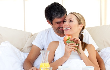 breakfast hotel: Beautiful couple having breakfast lying in the bed