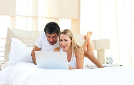 Joyful lovers using laptop lying on bed photo