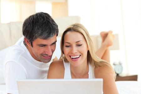 woman looking down: Close-up of lovers using a laptop lying on bed