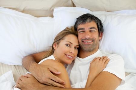 pareja en la cama: Pareja sonriente abrazando en la cama