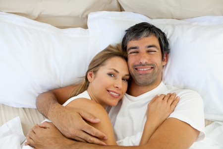 lying on bed: Smiling couple embracing lying in bed