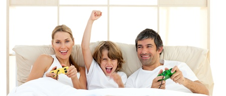 Smiling little boy playing video game with his family photo