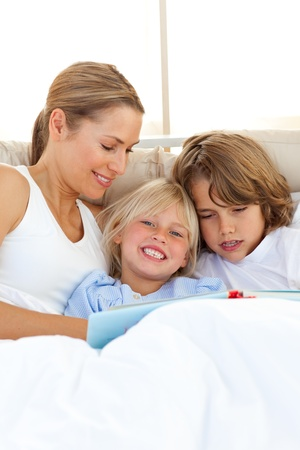Pretty mother and her children reading book Stock Photo - 10258794