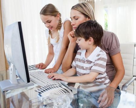 madre trabajadora: Atractiva madre ense�a a sus hijos a usar una computadora  Foto de archivo