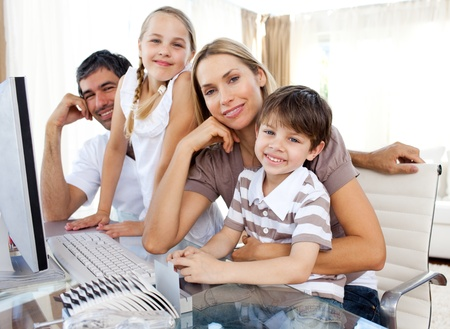 Attentive parents and their children using a computer Stock Photo - 10241397