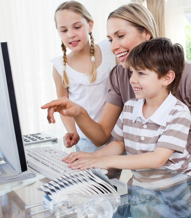 Happy mother and her children using a computer photo
