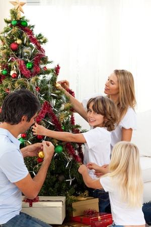 Happy family decorating Christmas tree photo