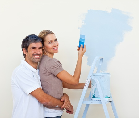 Smiling lovers painting a room photo