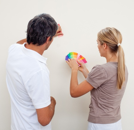 adult wall: Couple choosing a color to paint a room
